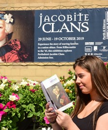 A young white woman with long dark brown hair reading a paper programme underneath a sign advertising the Jacobite Clans exhibition at Perth Museum (Katie Adams)
